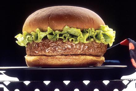 A hamburger with a rim of lettuce sitting on a black plate against a black background with a black and red napkin on a black and white-dotted tablecloth